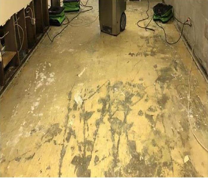 Concrete floor in home with SERVPRO equipment setup