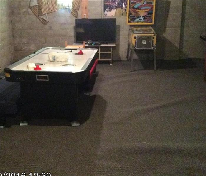 basement with wet grey carpeting and an air hockey table