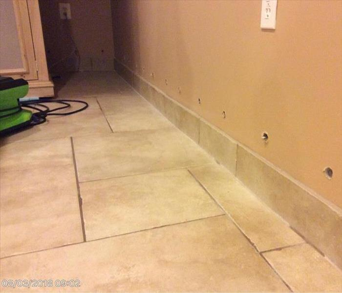 tile floor with water showing in the grout lines