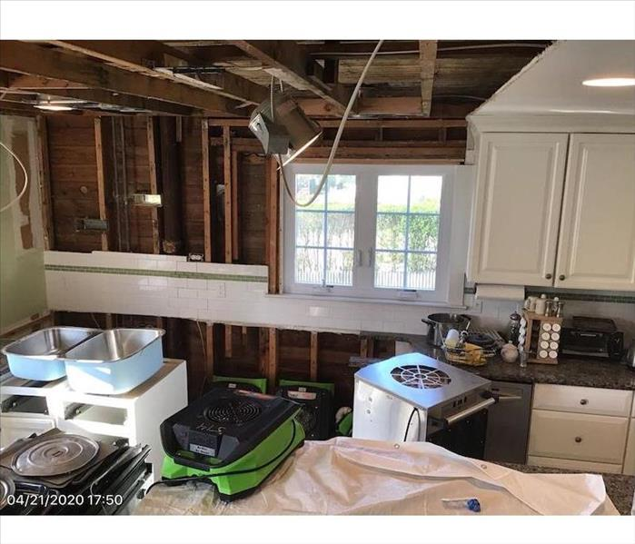 Kitchen with exposed framework and SERVPRO drying equipment